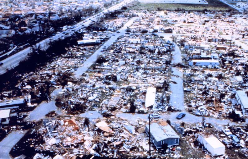 Destroyed houses, debris, water standing