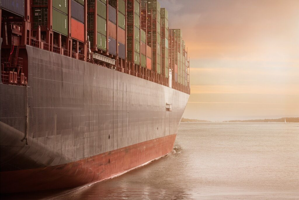 the starboard side of a container ship, moving into the sunset
