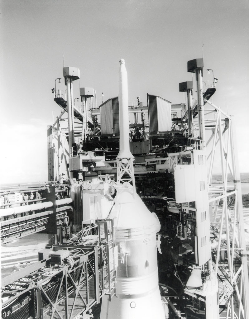 A technician can be seen working atop the white room across from the escape tower of the Apollo 11 spacecraft a few days prior to the launch of the Saturn V moon rocket.